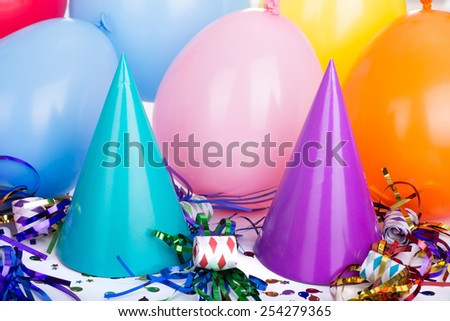 Colorful birthday party hats, balloons and noisemakers - stock photo