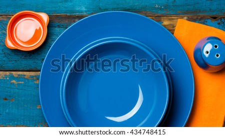 Colorful blue orange background with empty plates, napkin, sat shaker on wooden table. Top view, copy space.