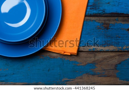 Colorful blue orange background with empty plates, napkin, sat shaker on wooden table. Top view, copy space. - stock photo
