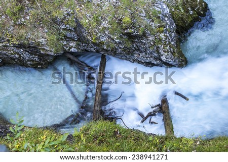 Colorful blue river with three trunks and water flowing in the rocky terrain. - stock photo