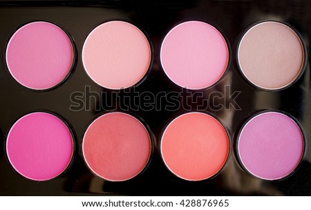 Colorful blush set on black background. Dry textured palette of professional cosmetics. Artistic retouching. - stock photo