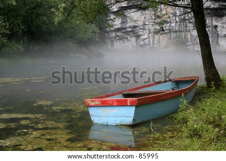 colorful boat on fog clouded lake - stock photo