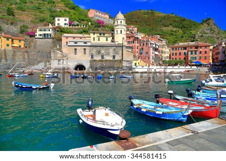Colorful boats near the pier and the church of Santa Margherita d'Antiochia in Vernazza, Cinque Terre, Italy - stock photo