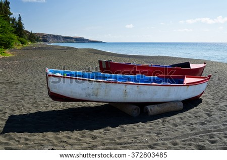 Colorful boats on the black sand beach of Saint Paul on Reunion Island - stock photo