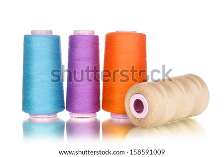 Colorful bobbin thread isolated on white - stock photo