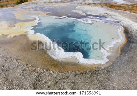 colorful boiling toxic thermal pool / geyser created from volcanic seismic activity, yellowstone national park, wyoming, united states - stock photo