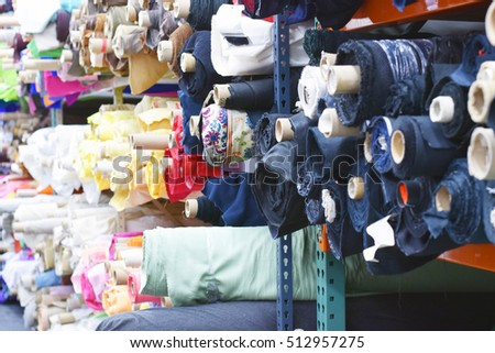 Colorful bolts of fabric cloth rolls in shop for sale