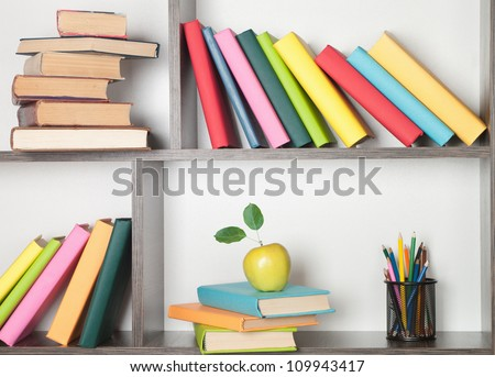 colorful book, apple and pencils on the bookshelf