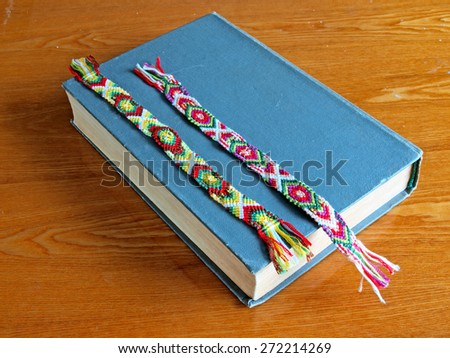 Colorful bookmarks braided from different threads on blue book wooden table       - stock photo