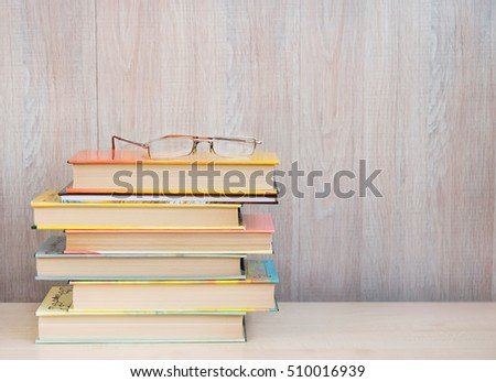 Colorful books on a wooden table.