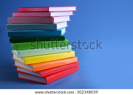 Colorful books on blue background - stock photo
