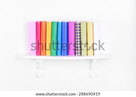 Colorful books on shelf on white wall background - stock photo