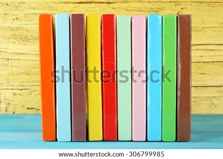 Colorful books on yellow wooden background - stock photo