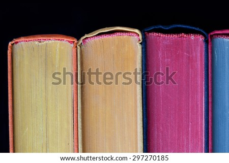 Colorful books. Yellow, violet, blue, yellow pages. Close up, textures and detailes, hard cover. Black background. Copy space. Isolated - stock photo