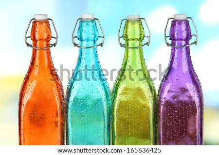 Colorful bottles on bright background - stock photo