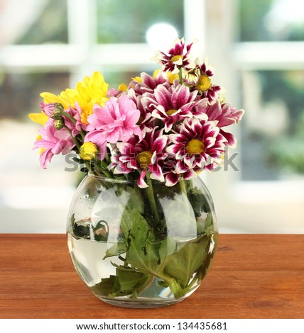 colorful bouquet of chrysanthemums in a glass vase on wooden table close-up