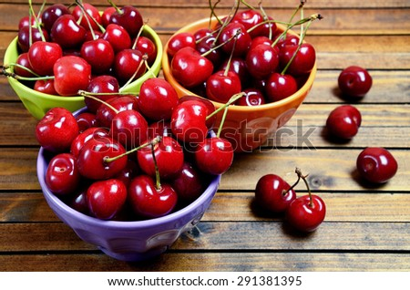 Colorful bowl with cherries fruit on wooden table - stock photo