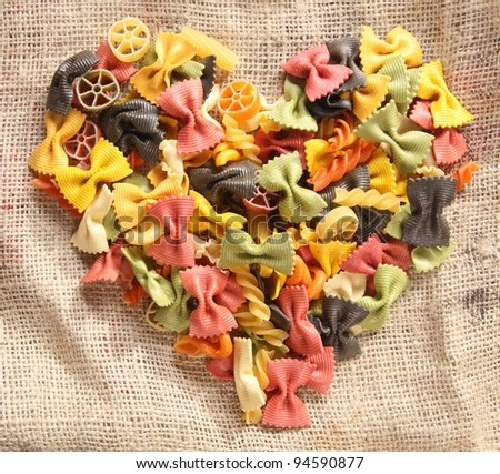 Colorful Bowtie Pasta Heart. Heart-shaped arrangement of colourfaul bowtie pastas, or farfalle, on rustic hessian material, concpetual of love and romance. - stock photo