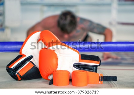 Colorful boxing gloves next to ring with blurred man doing push ups as background - Defocused boxer with tattoos exercising and fighting equipment foreground - Concept of tough sport training - stock photo