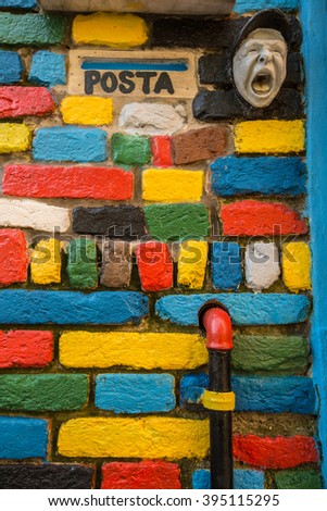 Colorful brick wall with colorful pipiline and postage sign in vertical position