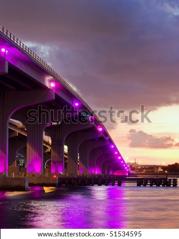 Colorful bridge in Miami Florida with purple lights at sunset, connecting downtown and Miami Beach
