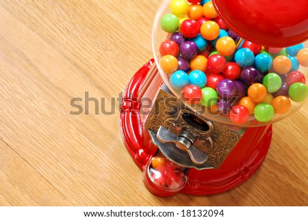 Colorful bubble gum in gumball machine with wood grain background.  Close-up with shallow dof.  Copy space included. - stock photo