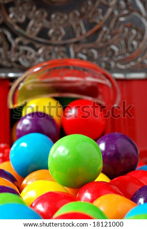Colorful bubble gum spilling from a gumball machine.  Macro with extremely shallow dof.  Selective focus on green gumball. - stock photo