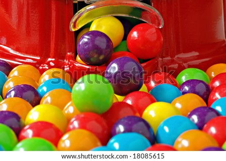 Colorful bubble gum spilling from a gumball machine.  Macro with shallow dof.  Selective focus on dispenser opening. - stock photo