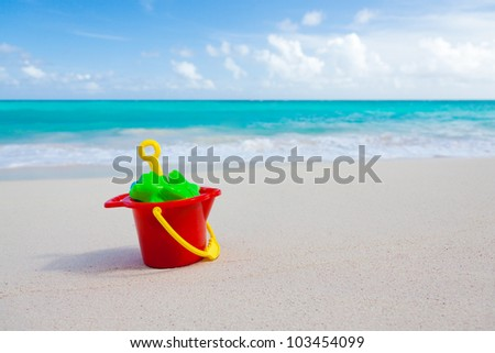 colorful bucket and other sand toys on beach with the sea in the background