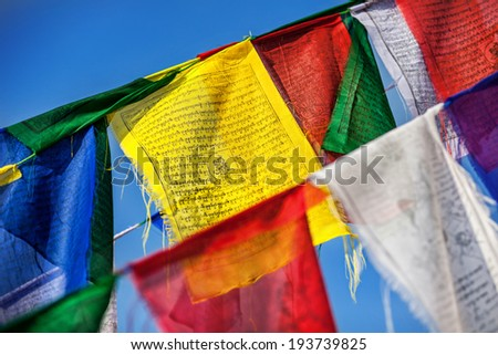 Colorful Buddhist prayer flags at blue sky near Bodhnath stupa in Kathmandu valley, Nepal
