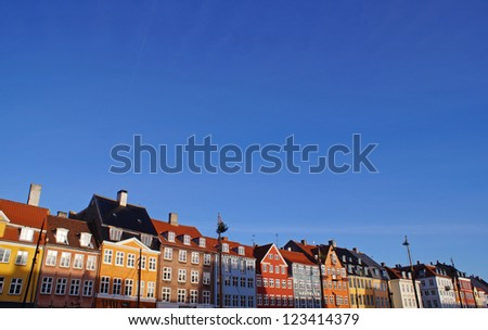 Colorful buildings next to Nyhavn Waterfront and clear blue sky - stock photo