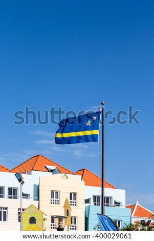 Colorful Buildings with Curacao Flag under blue skies
