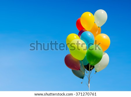Colorful bunch of helium balloons isolated on background, with copy space - stock photo