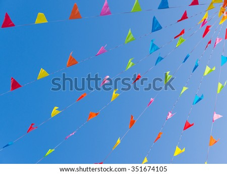 colorful bunting flags against a blue saturated sky - stock photo
