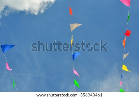 Colorful bunting flags against blue sky background - stock photo
