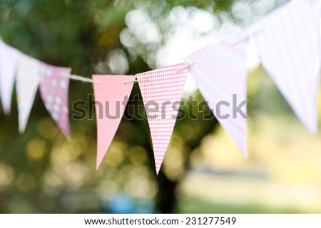 Colorful bunting flags against green trees - stock photo