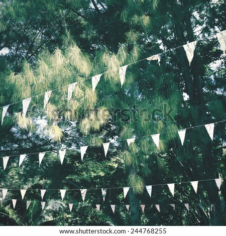 Colorful bunting flags hanging on tree with retro filter effect - stock photo