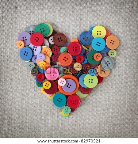 Colorful buttons heart on sacking - stock photo