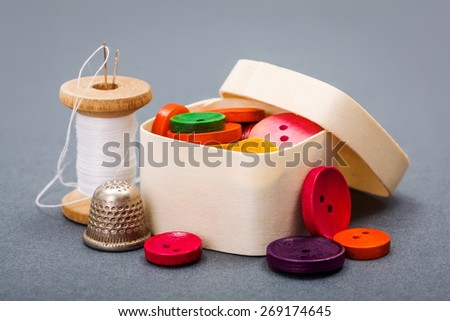 Colorful buttons in wooden box near sewing thread and thimble - stock photo