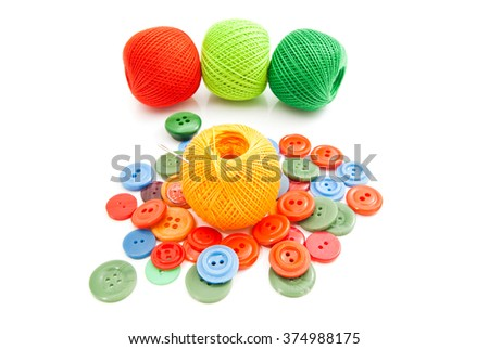 colorful buttons, needle and tangles of thread on white - stock photo