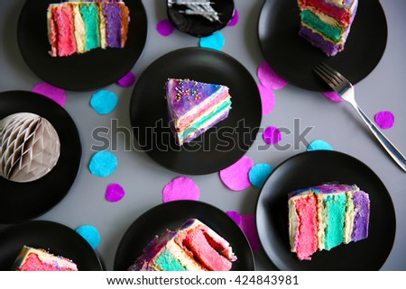 Colorful cake slices on black plates on gray background