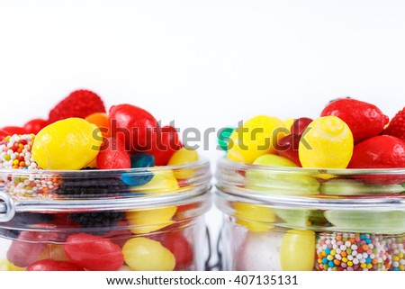 Colorful candies and chewing gum in the glass jars close-up on a white background with space for your text