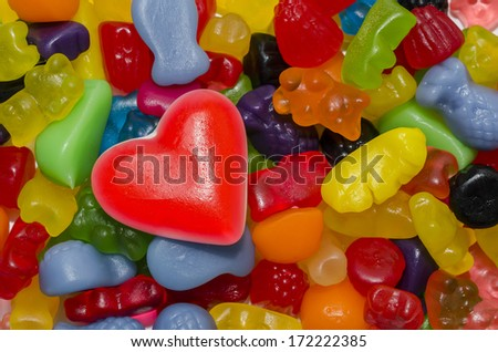 colorful candies and in the foreground a red heart-shaped candy - stock photo