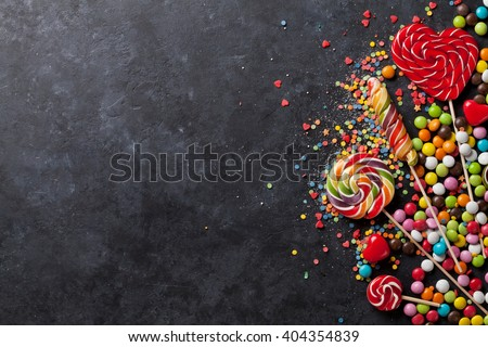 Colorful candies and lollipops over stone background. Top view with copy space - stock photo