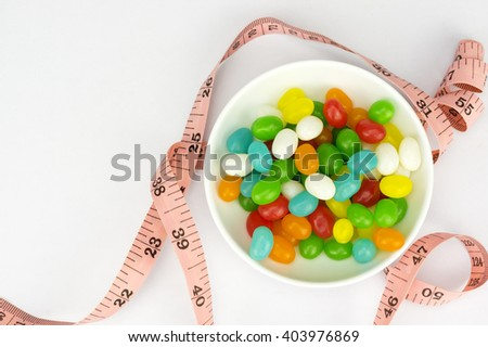Colorful candies and tape measure with shallow depth of field (dof)-diet and healthy teeth concept