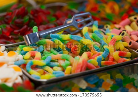 """Colorful candies. Background made of colorful sweets and candies with small depth of field. Green red yellow and blue """"worms"""" in the center of composition. Jerusalem market. Mahane Yehuda Market. - stock photo"""