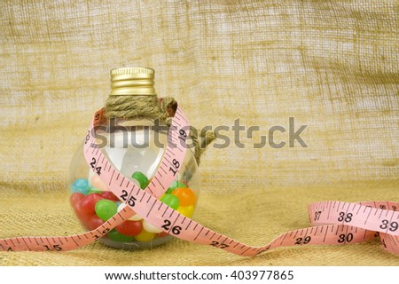Colorful candies in bottles and tape measure with shallow depth of field (dof)-diet and healthy teeth concept - stock photo