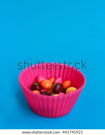 Colorful candies in cupcake case on the blue background - stock photo