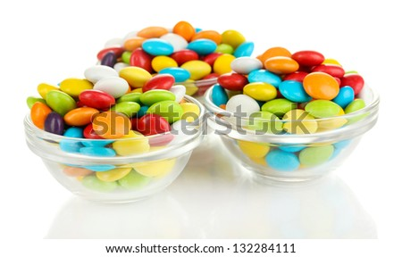 Colorful candies in glass bowls isolated on white