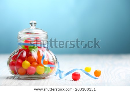 Colorful candies in jar on table on blue background - stock photo